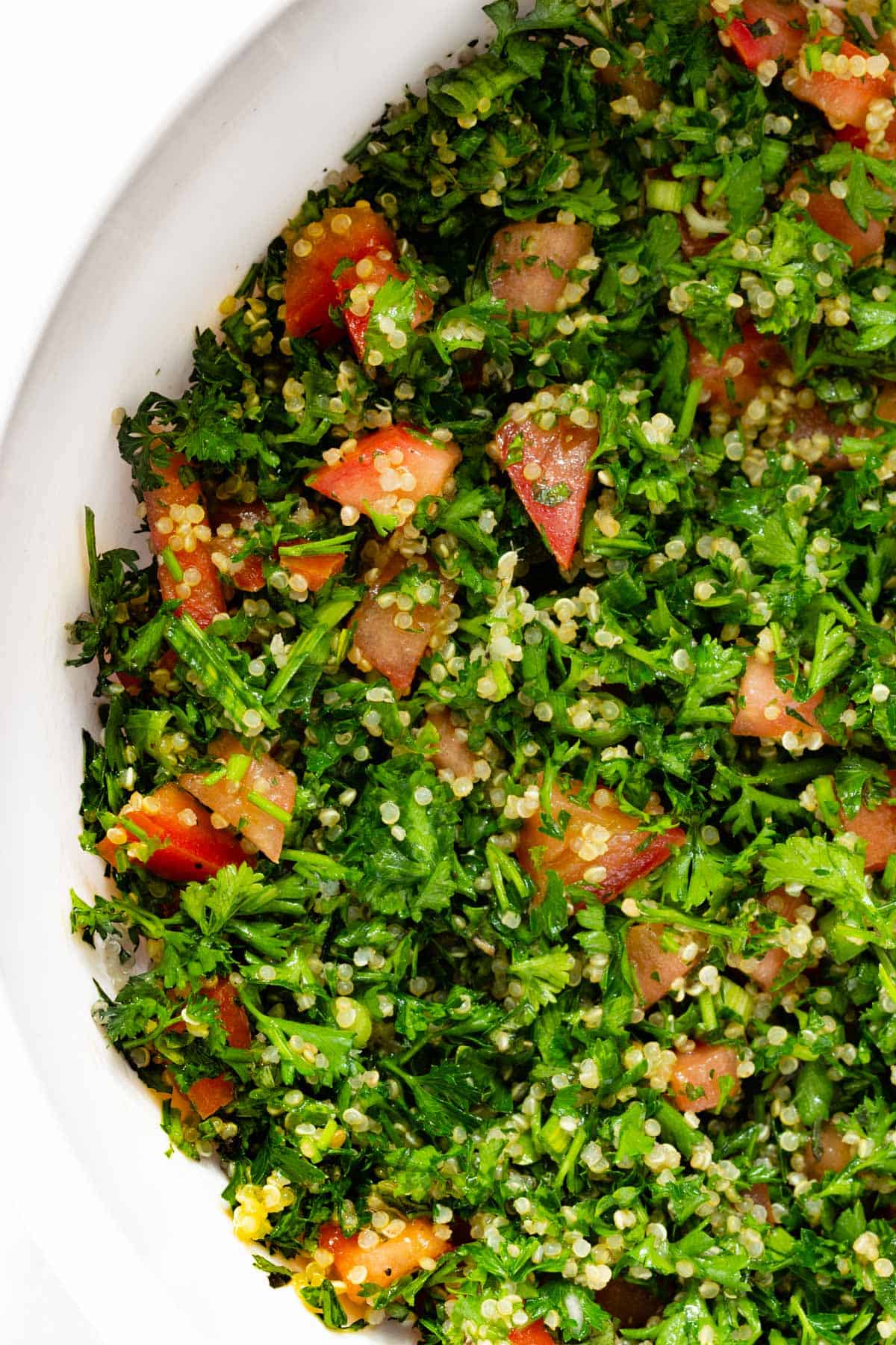 A close up of quinoa tabbouleh in a white serving bowl.