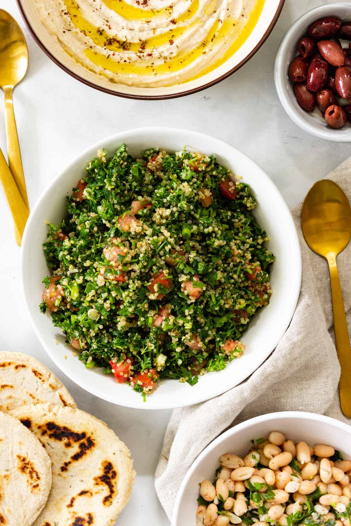 A bowl of quinoa tabbouleh sits on a table with other small plates of food.