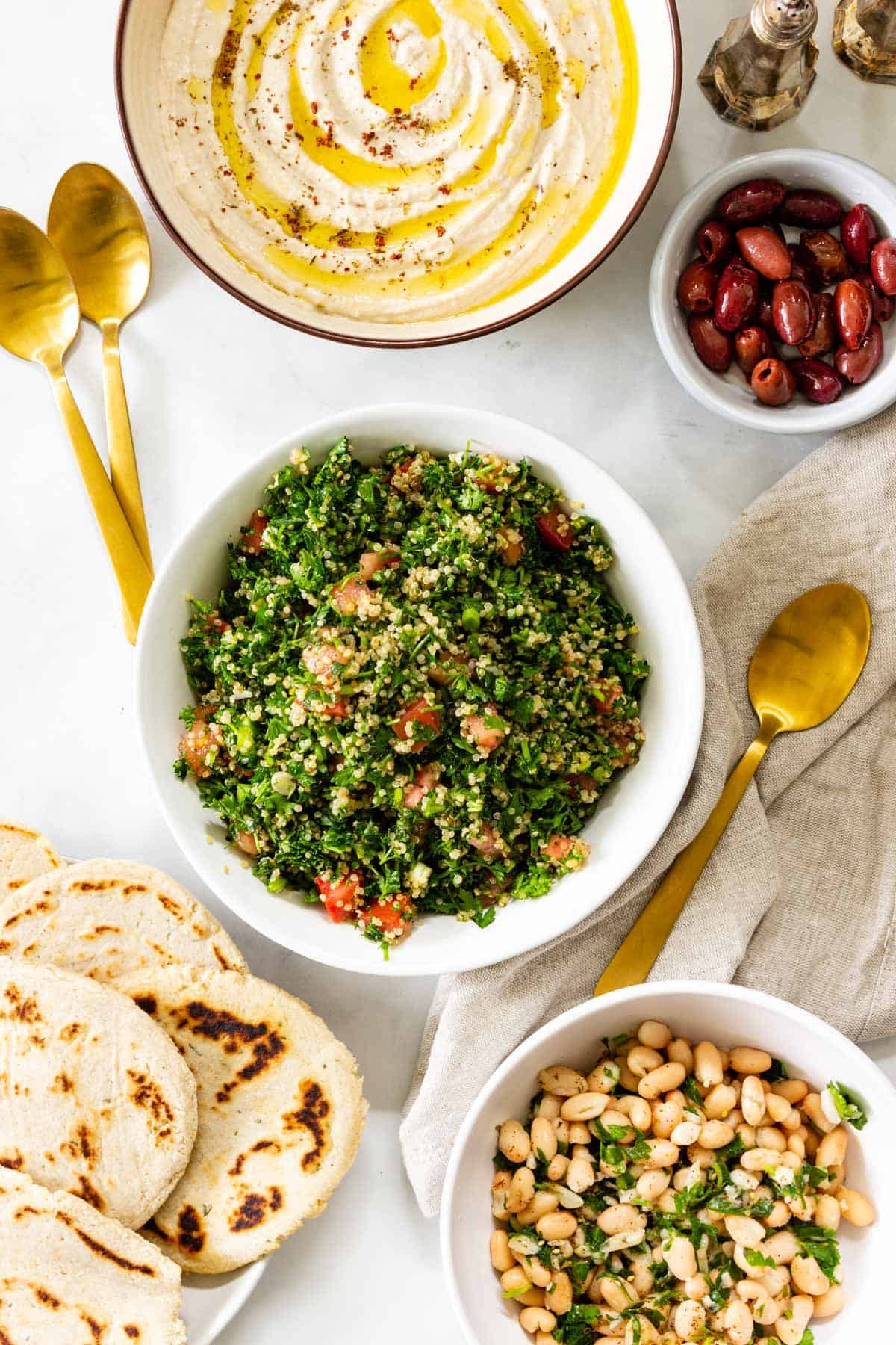 Plates of hummus, tabbouleh, olives, flatbread, and marinated beans are arranged on a table with gold silverware.
