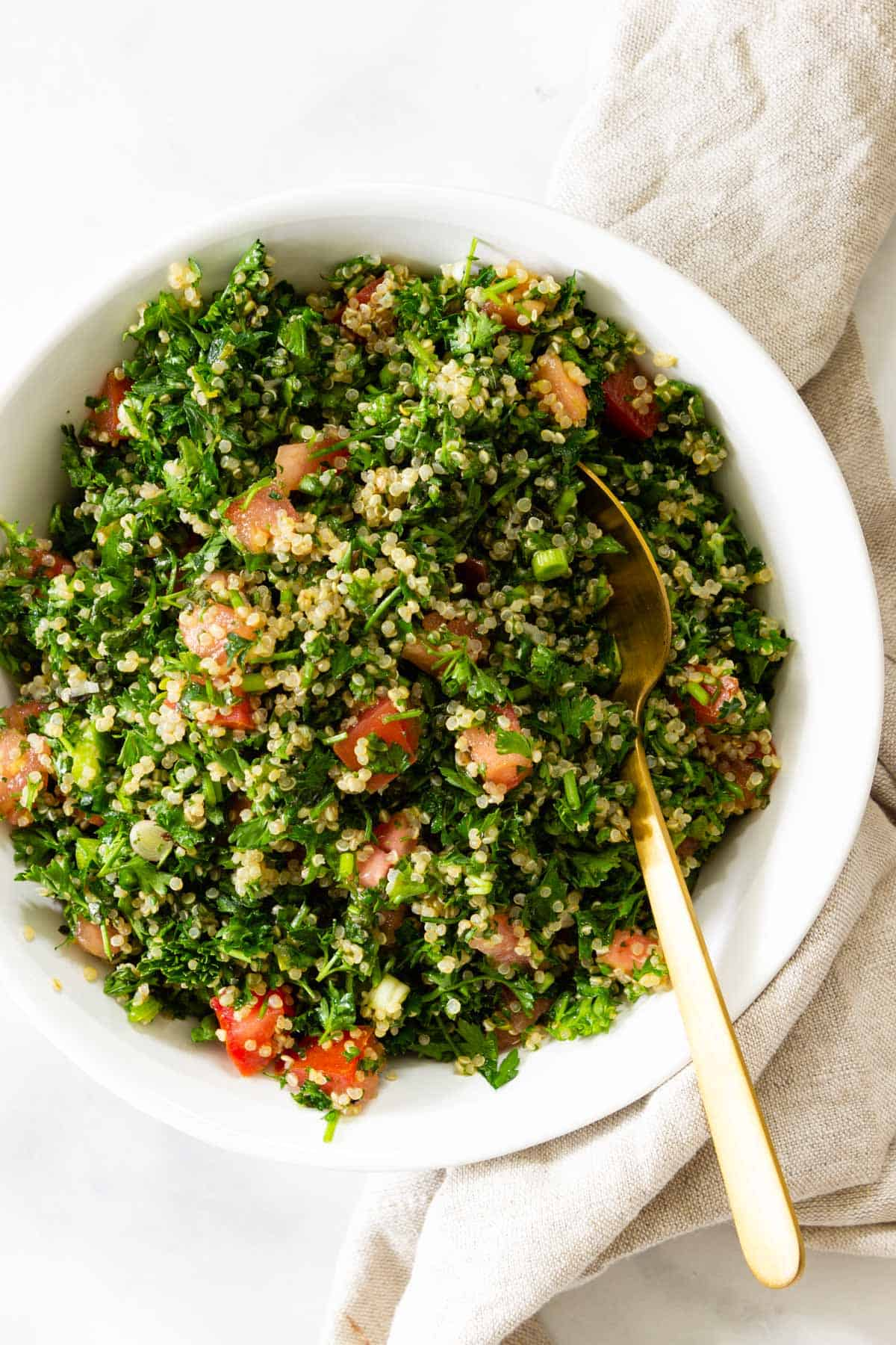 A white bowl of quinoa tabbouleh served with a gold spoon.
