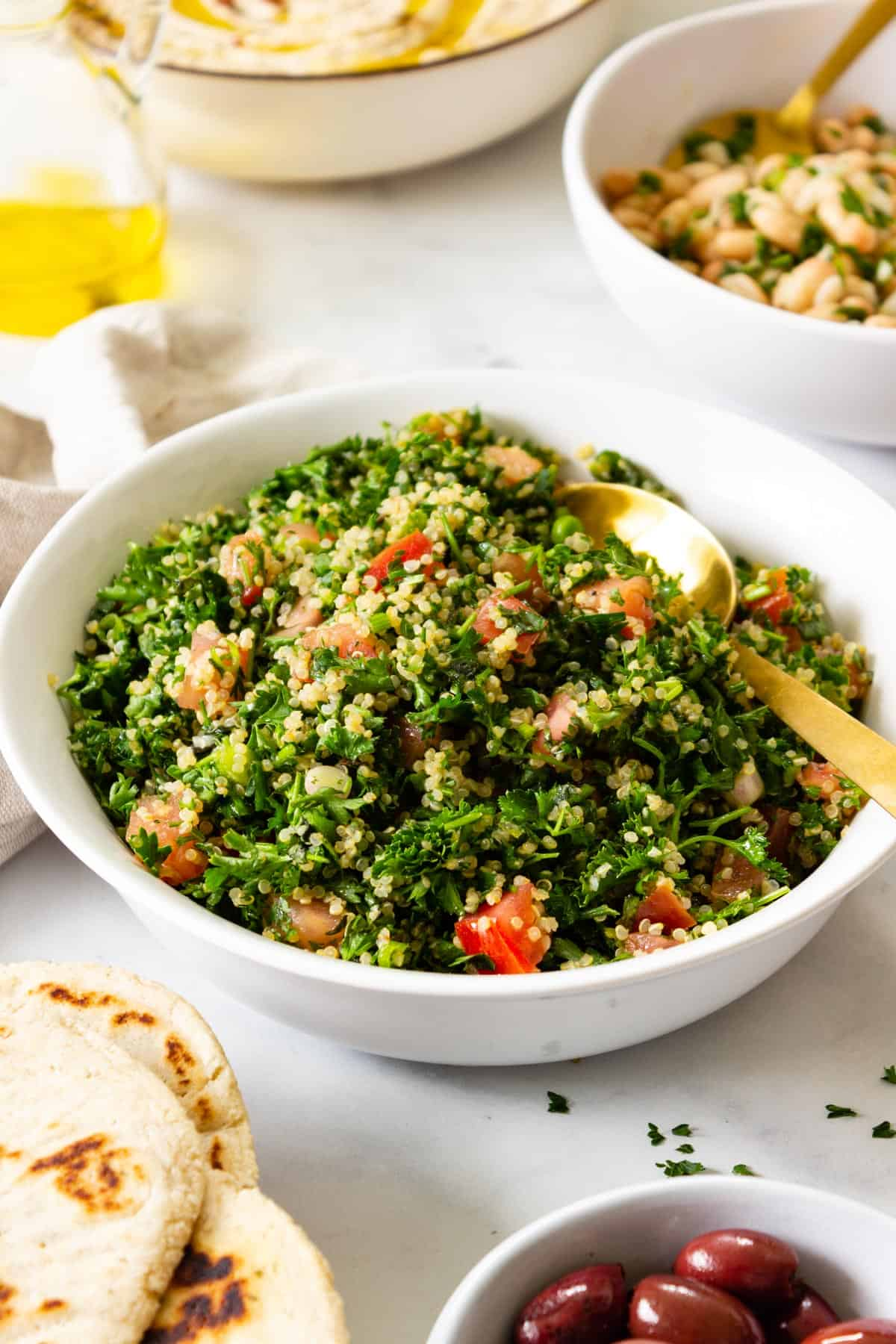 A white serving bowl of tabbouleh sits on a table with other side dishes.
