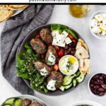 A Mediterranean feast with koftas, tabbouleh, olives, cubed feta, cucumbers, tomatoes, and flatbread.