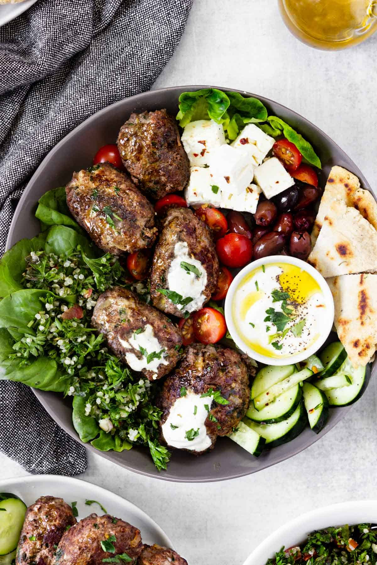A Mediterranean meal with beef koftas is served on a grey dish.