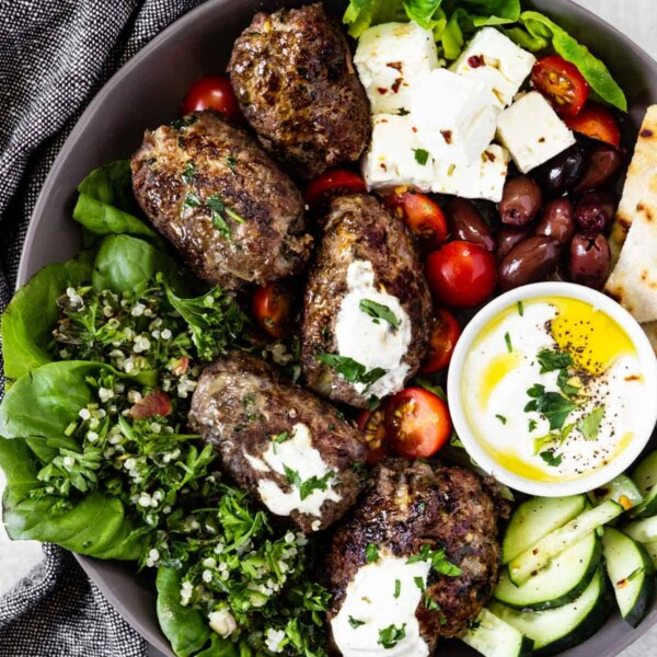 A large shallow bowl loaded with beef koftas, cucumber slices, tabbouleh, chunks of feta, olives, cheery tomatoes, and a dish of Greek yogurt sauce.