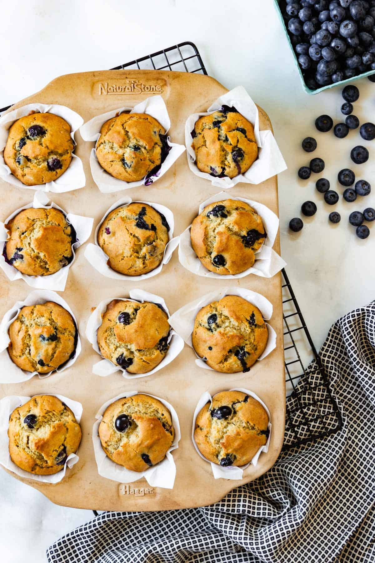 A muffin pan with freshly baked muffins sits on a wire cooling rack. A carton of blueberries sits nearby.