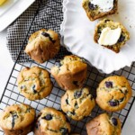 Blueberry banana muffins are laid out on a cooling rack.