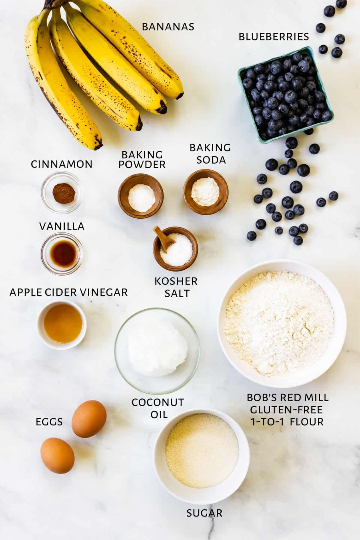 Ingredients for gluten-free blueberry banana muffins are laid out on a marble countertop.