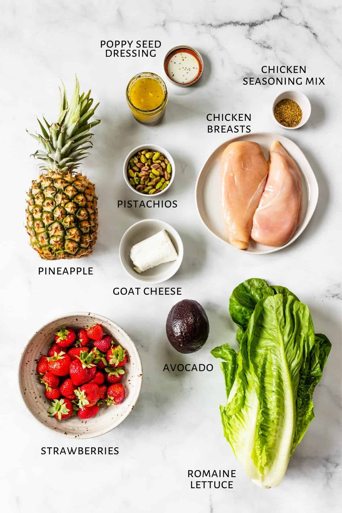 Ingredients for strawberry chicken salad are laid out on a marble countertop.