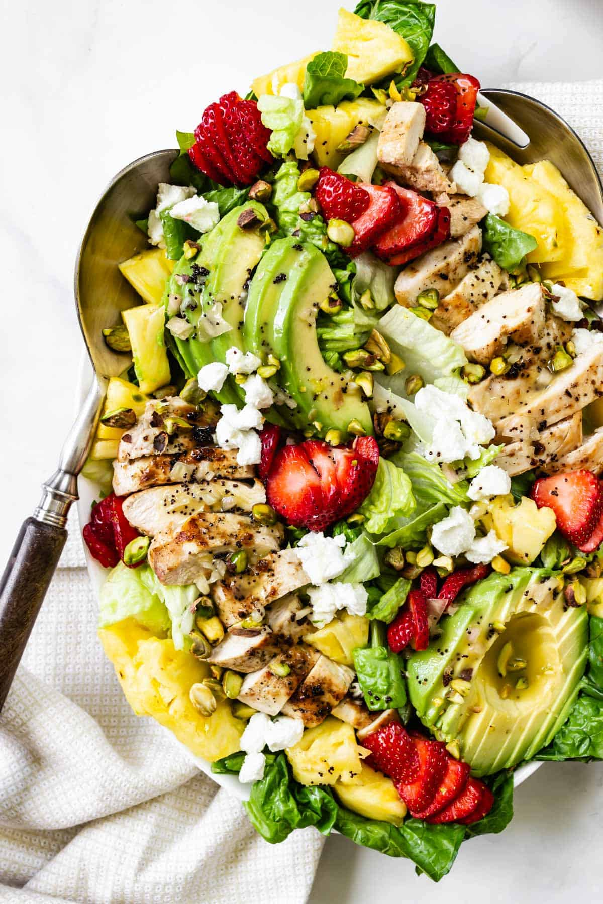 A salad loaded with pineapple, strawberries, grilled chicken, and avocado.