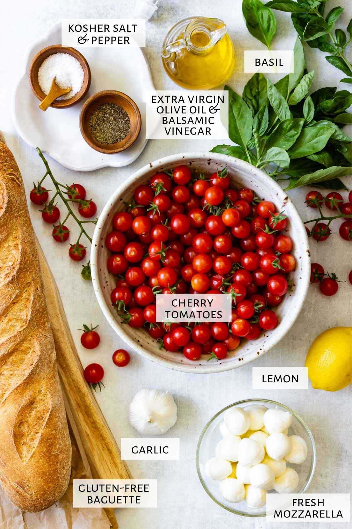 Ingredients for bruschetta with mozzarella are are set out on a marble countertop.