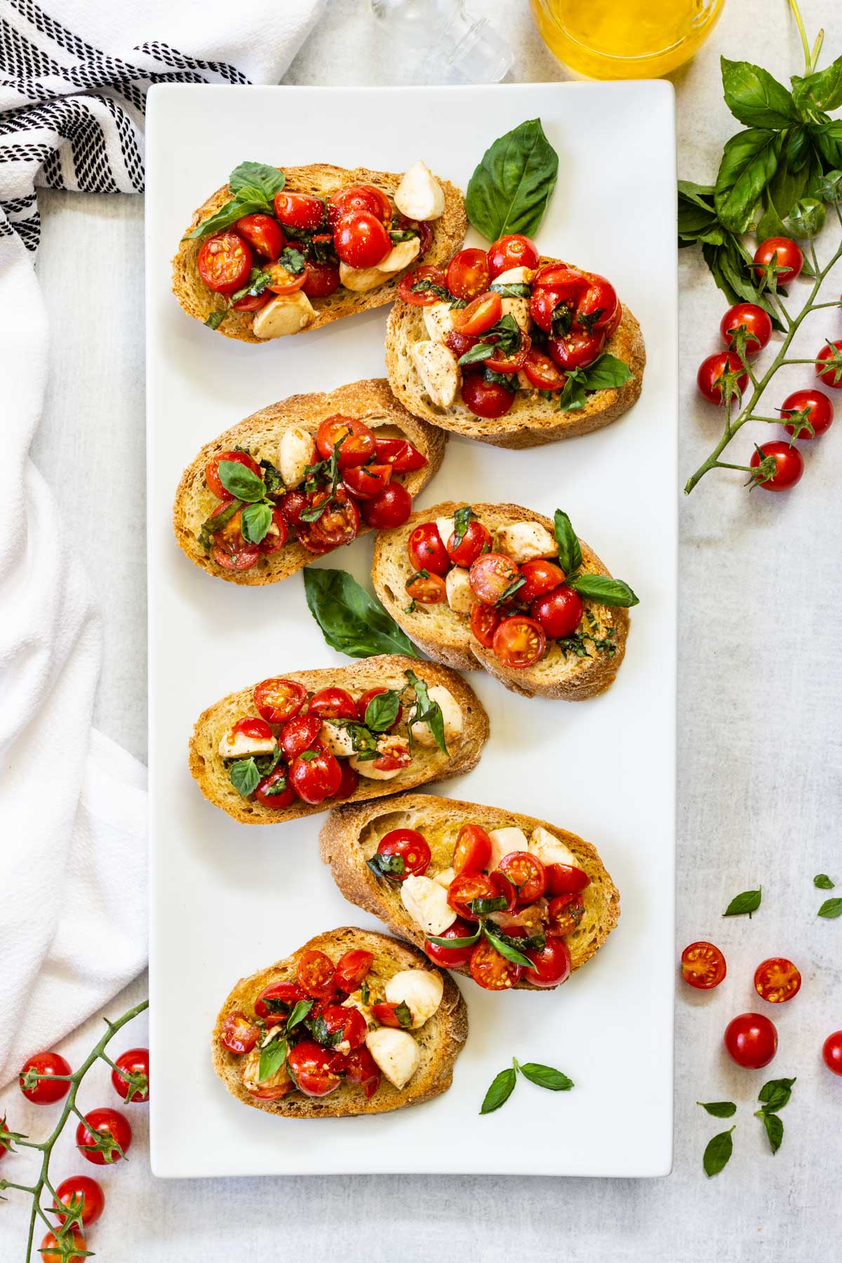 A white rectangular plate is serving a bruschetta with cherry tomatoes and mozzarella mixture.