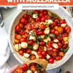 A bowl of cherry tomatoes and mozzarella mixed with olive oil and basil. A spoonful is topping bruschetta.