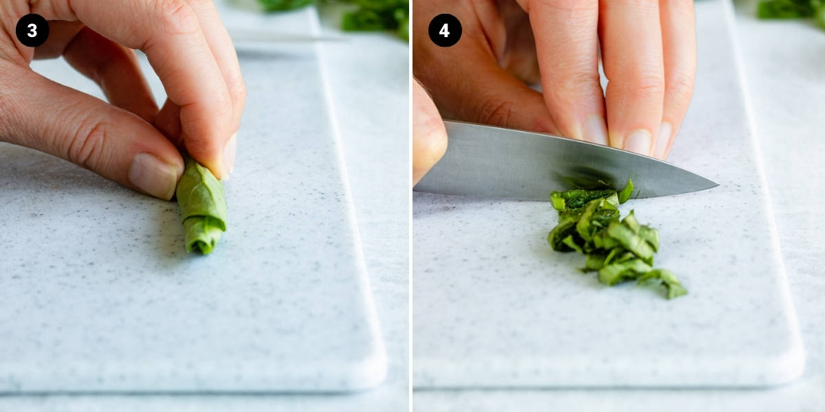 A hand holds basil leaves in the shape of a tight cylinder. The basil is thinly sliced.