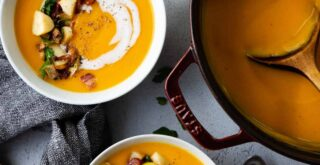 A bowl of butternut squash soup on a wooden tabletop with a napkin loosely draped next to it. A silver spoon and a small bowl of soup toppings are next to it.
