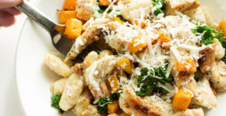 Sliced grilled chicken with gnocchi, sautéed butternut squash, and kale in a creamy sauce topped with grated parmesan.